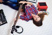 girl lying on the floor with bass guitar