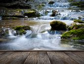 The beautiful waterfall in forest and wood pier, spring, long exposure