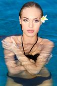 Exotic gorgeous young woman with frangipani in her hair standing chest high in the water in the swimming pool looking at the camera with a sensual expression