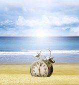 Clock stuck in sand at beach, bright sky behind