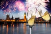 Toasting with champagne in London - Westminster abbey with fireworks in the background
