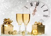 Glasses with champagne and gift box against fireworks and clock close to midnight