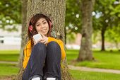 Beautiful relaxed young woman enjoying music in the park