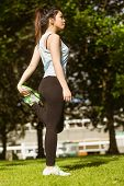 Side view of healthy young woman stretching leg in park