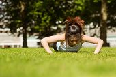 Portrait of healthy young woman doing push ups in park