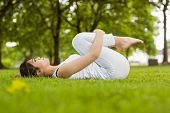 Full length side view of toned young woman doing stretching exercises in park