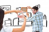 Happy young couple putting up picture frame against living room sketch