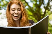 Cheerful female college student reading book in the park