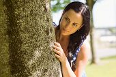 Pretty brunette leaning against a tree in the park