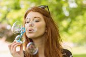 Cute young woman blowing bubbles at the park