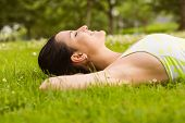 Peaceful fit brunette lying on the grass in the park