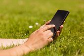 Close up of a pretty redhead holding her mobile phone on grass