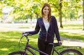 Pretty redhead with her bike on a sunny day