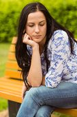 Thoughtful casual brunette sitting on bench in the park