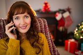 Smiling redhead phoning at christmas at home in the living room