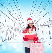 Brunette in winter clothes holding many gifts and shopping bags against blue abstract light spot design