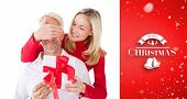 Smiling woman covering partners eyes and holding gift against red vignette