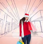 Happy brunette in winter wear holding shopping bags against twinkling blue and red lights
