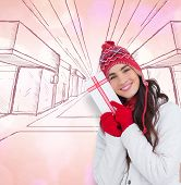 Festive brunette in winter clothes pointing gift against twinkling yellow and purple lights