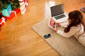 Pretty woman lying on floor using technology at Christmas at home in the living room