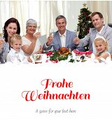 Family tusting in a Christmas dinner with white wine against christmas greeting in german