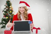 Festive blonde shopping online with laptop and pointing at it against snow falling