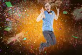 Geeky hipster jumping and smiling against colourful fireworks exploding on black background