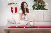 Pretty brunette shopping online with laptop at chistmas against snow