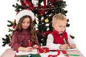 Festive little siblings drawing pictures against snow