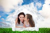 Mother and her daughter having fun on bed against green grass under blue sky