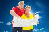 Lost tourist couple using map against cloudy sky with sunshine
