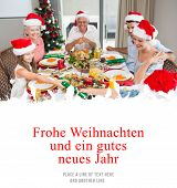 Cheerful family at dining table for christmas dinner against christmas greeting in german