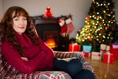 Pretty redhead in jumper sitting on the armchair at christmas at home in the living room
