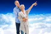 Happy mature couple embracing and looking against bright blue sky over clouds