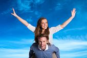 Smiling young man carrying woman against blue sky