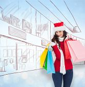 Smiling brunette in winter wear holding shopping bags against blue abstract light spot design
