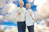 Happy mature couple smiling at camera showing money against blue sky with white clouds