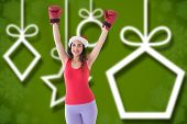 Festive brunette in boxing gloves cheering against blurred christmas background