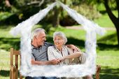 Senior couple sitting on a bench against house outline in clouds