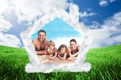 Happy family beside the swimming pool against green field under blue sky