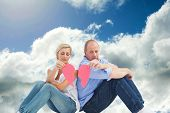 Sad mature couple holding a broken heart against blue sky with clouds