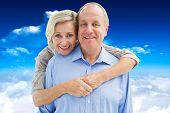Happy mature couple embracing smiling at camera against bright blue sky with clouds