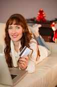 Smiling redhead lying on couch shopping online with laptop at christmas at home in the living room