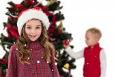 Festive little girl smiling at camera with boy behind against snow