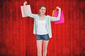 Smiling young woman holding up shopping bags against blurred red planks