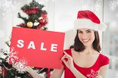 Festive brunette holding sale sign against snowflakes