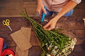 Female florist cutting floral stems with secateurs