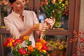 Female florist tying roses up with ribbon