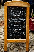 French menu board on cobblestones