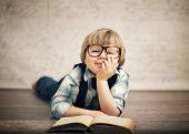 stock photo of little kids  - Cheerful smiling little kid reading a book - JPG